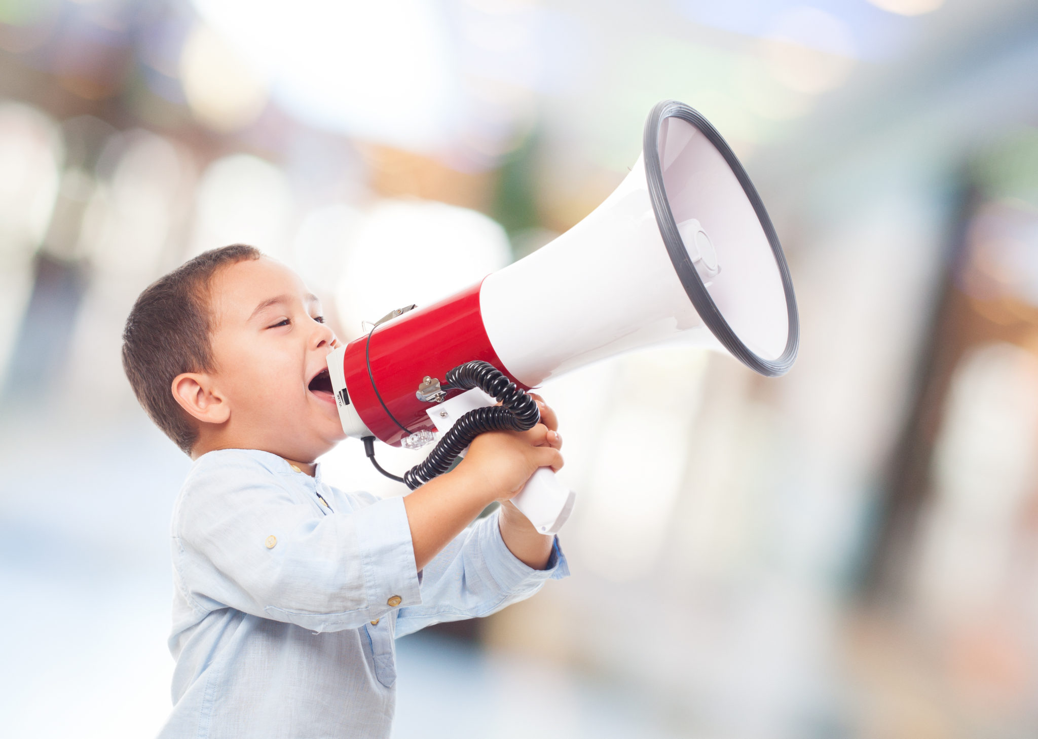 portrait of a little boy shouting on the megaphone